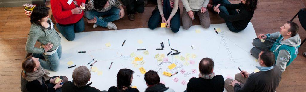 Plusieurs personnes rassemblées autour d'une grande feuille avec post-it et stylos.